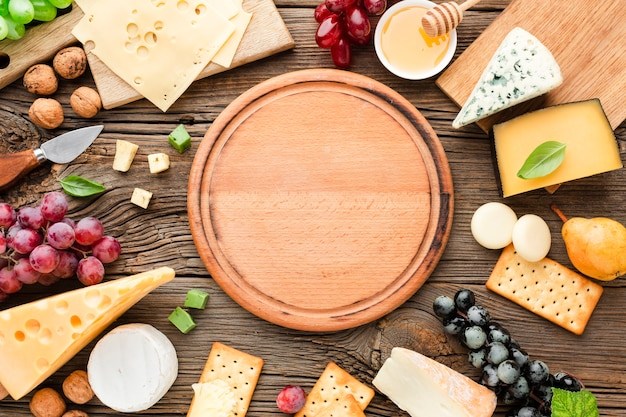 Flat lay cheese mix  with wooden cutting board Free Photo