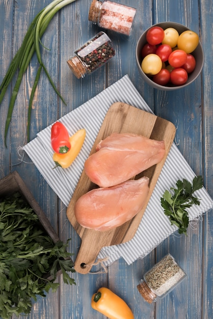 Flat lay chicken breast on wooden board with peppers and tomatoes Free Photo
