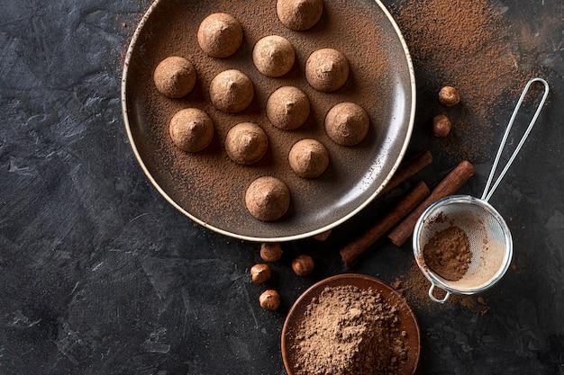 Piatto disteso di caramelle al cioccolato con cacao in polvere e bastoncini di cannella Foto Gratuite