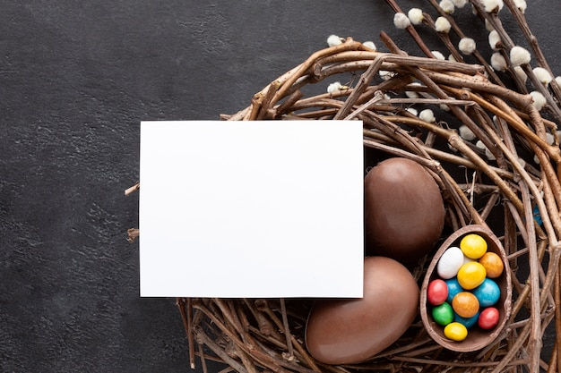 Flat lay of chocolate easter eggs filled with colorful candy in nest Free Photo