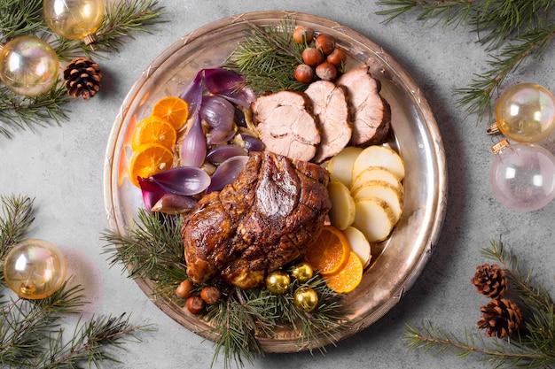 Lay piatto di bistecca di natale sulla piastra con globi e decorazioni di pigne Foto Gratuite
