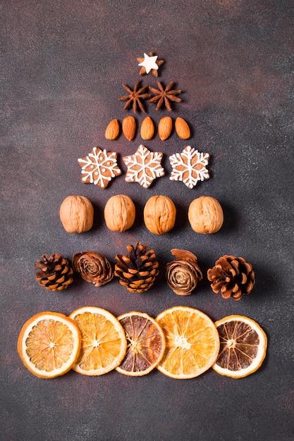 Lay piatto di forma di albero di natale fatto di pan di zenzero e agrumi secchi Foto Gratuite