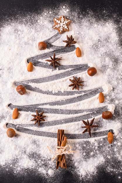 Flat lay of christmas tree shape with flour and star anise Premium Photo