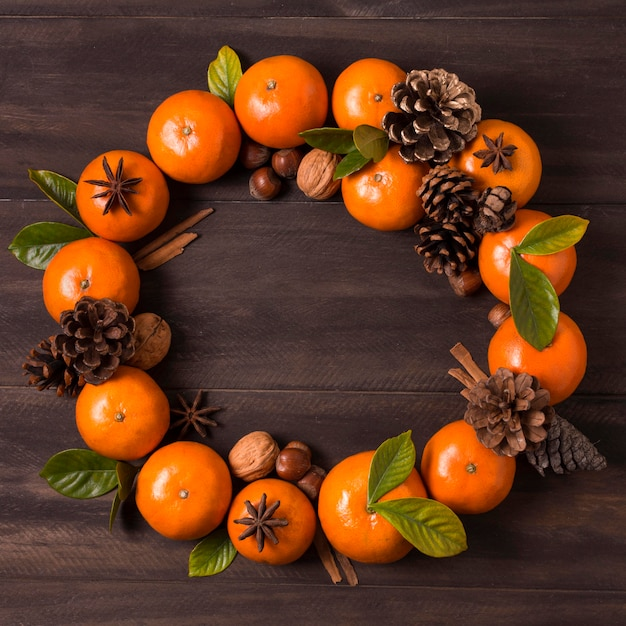 Lay piatto di ghirlanda di natale fa di mandarini e pigne Foto Gratuite