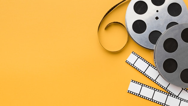 Flat lay cinema elements on yellow background with copy space Premium Photo