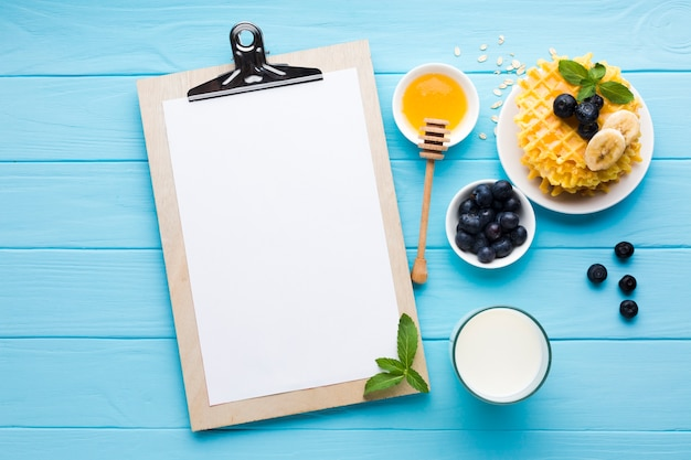 Flat lay clipboard mockup on breakfast table Free Photo