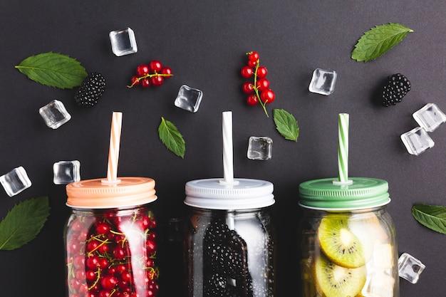 Flat-lay close-up mason jars with berries and kiwi Free Photo