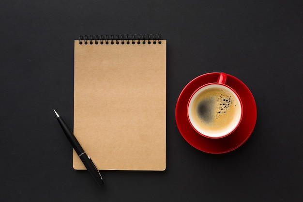 Flat lay of coffee cup and notebook on work desk Free Photo