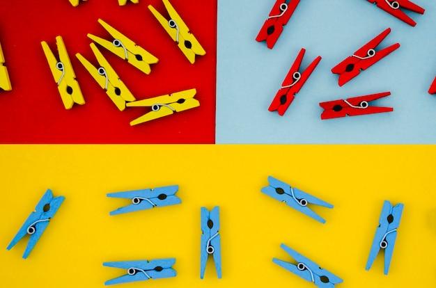 Flat-lay colorful clothes pins on colored backgrounds Free Photo