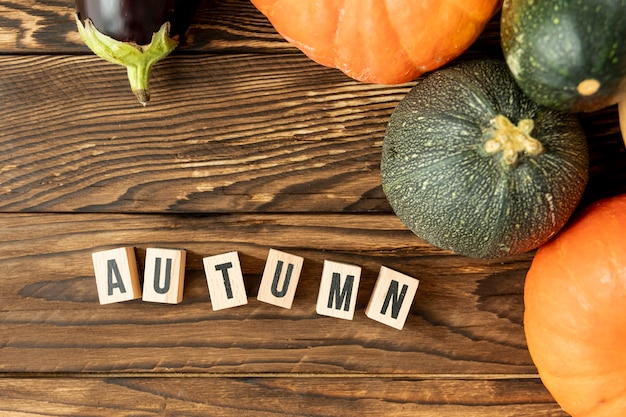 Flat lay colorful pumpkins with autumn lettering Free Photo