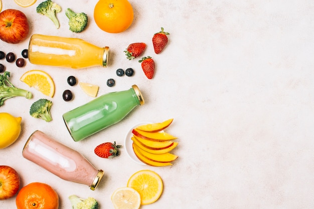 Flat lay colorful smoothies and fruits with copy space Free Photo