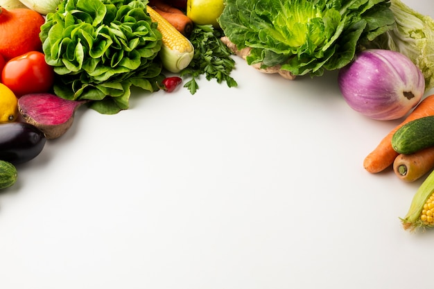 Flat lay colorful veggies on white background with copy space Free Photo