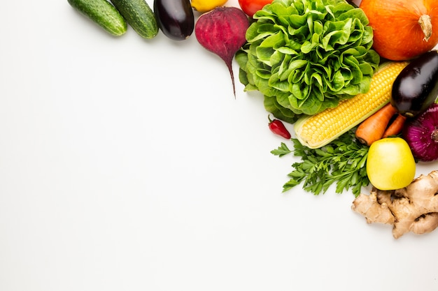 Flat lay colourful veggies on white background with copy space Free Photo