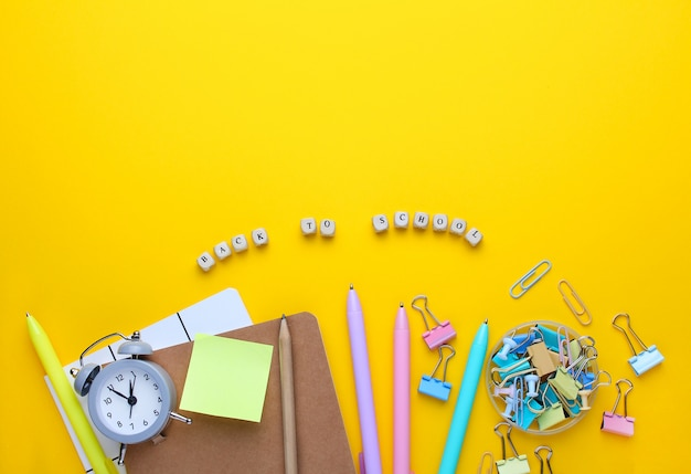 Flat lay composition of notebook, pencil, pens, binders, alarm clock. Premium Photo