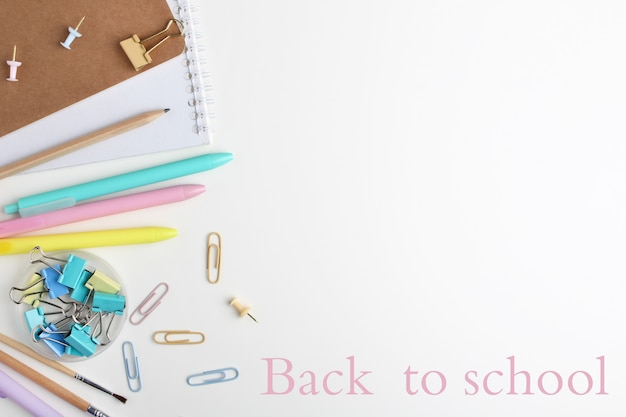 Flat lay composition of notebooks, pens, pencil, binders, sticky notes, paper clips and brushes. Premium Photo