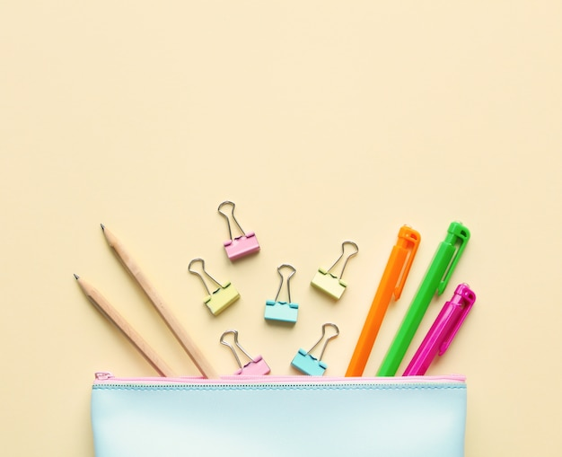 Flat lay composition of pastel blue pencil case with pens, pencils,paper binders. Premium Photo