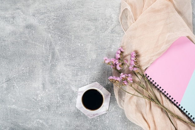 Flat lay composition with feminine scarf, coffee cup, pink dry flowers, paper notebook on concrete surface. Premium Photo