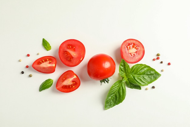 Flat lay composition with fresh cherry tomatoes, pepper and basil on white space, space for text. ripe vegetables Premium Photo