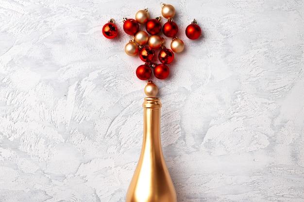 Плоская композиция с золотой бутылкой шампанского и елочными шарами Premium Фотографии