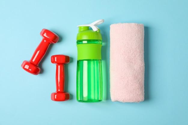 Плоская композиция с полотенцем, гантелями и фитнес-бутылкой на синем фоне Premium Фотографии