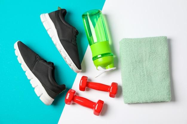 Плоская композиция с полотенцем, гантелями, фитнес-бутылкой и кроссовками на цветном фоне Premium Фотографии