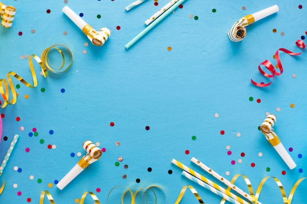 Flat lay of confetti and party whistles Premium Photo