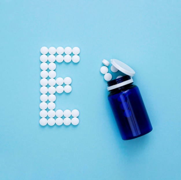 Flat lay of container with pills spelling letter e Free Photo