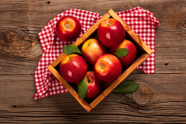 Flat-lay crate with ripe apples on cloth Free Photo