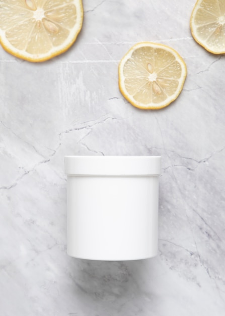 Flat lay of cream box and lemon slices on marble background Free Photo