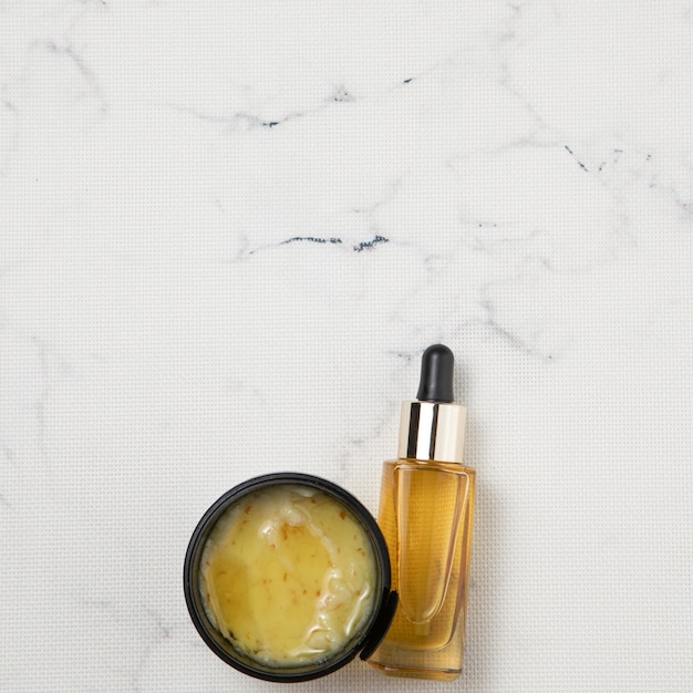 Flat lay of cream and essential oil bottle on marble background Free Photo