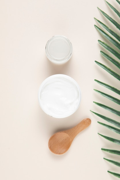 Flat lay of a cream and spoon on plain background Free Photo