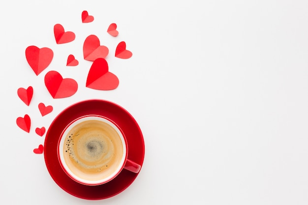 Flat lay of cup of coffee with valentines day paper heart shapes Free Photo