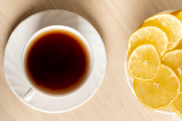 Flat lay cup of tea with lemon arrangement on plain background Free Photo