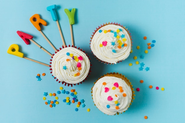 Flat lay cupcakes and party lettering Free Photo