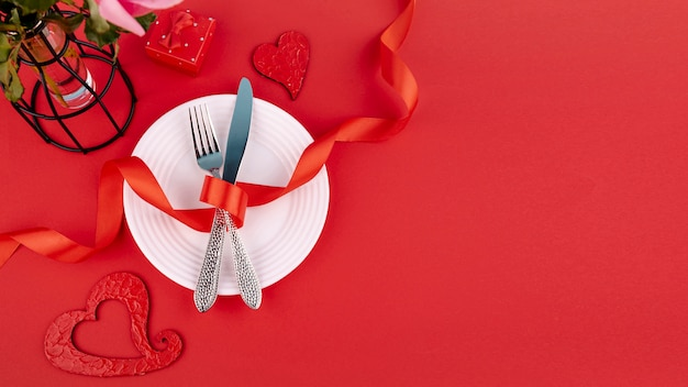 Flat lay of cutlery on plate with ribbon and hearts Free Photo