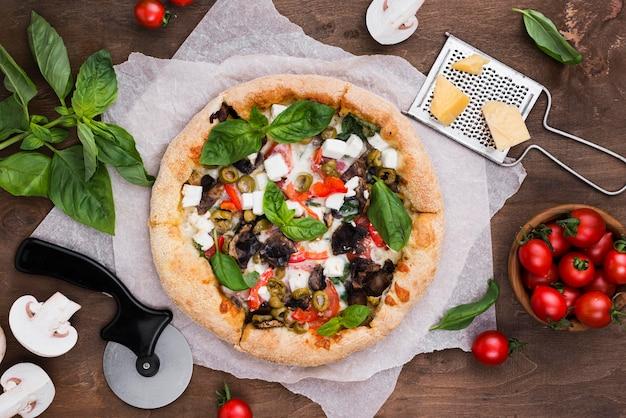 Плоско лежала вкусная пицца и овощи Premium Фотографии