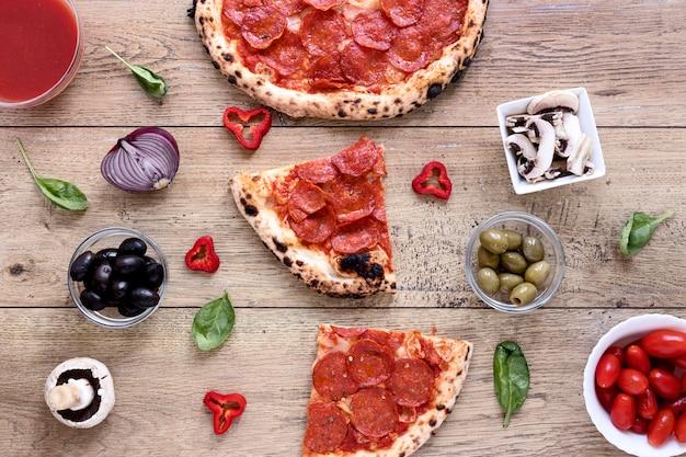 Плоская кладут вкусную пиццу на деревянный фон Бесплатные Фотографии