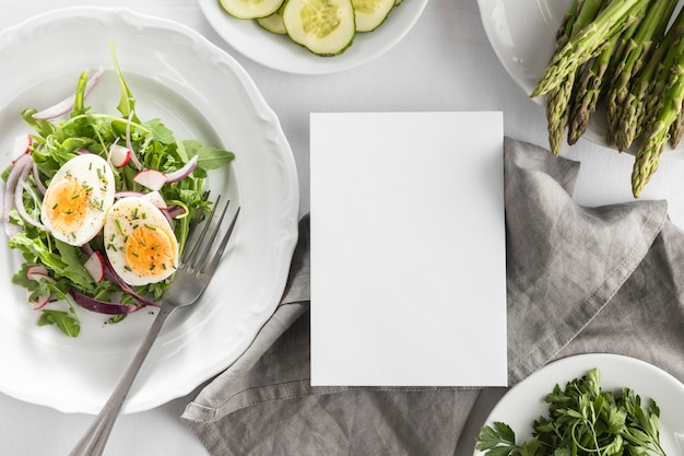 Flat lay delicious salad on a white plate with empty card Free Photo