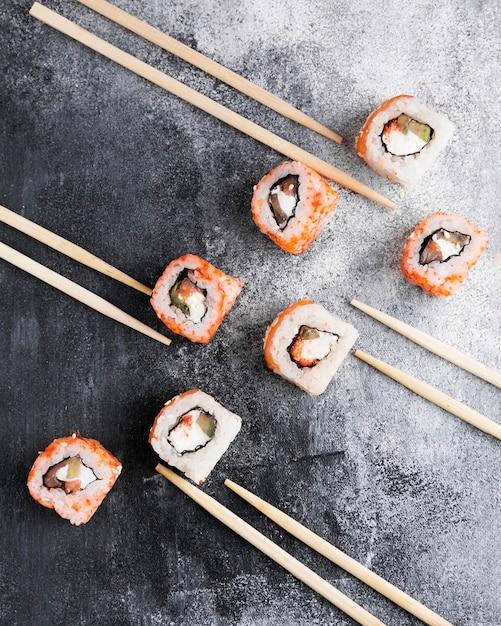 Плоские лежали вкусные суши и палочки для еды Бесплатные Фотографии