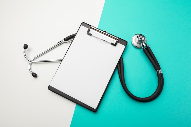 Flat lay design of stethoscope and blank clipboard pad with for medical concept. Premium Photo