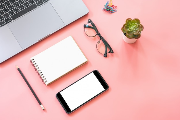 Flat lay design of workspace desk with laptop, blank notebook, smartphone, pencil, stationery Premium Photo