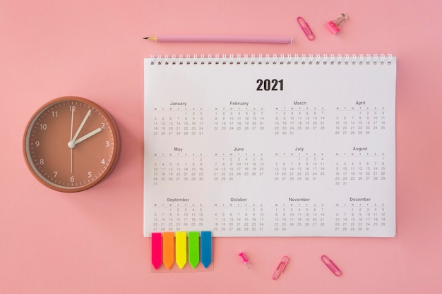 Flat lay desk calendar on pink background Free Photo