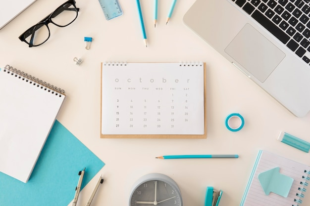 Flat lay desk calendar with blue office accessories Free Photo
