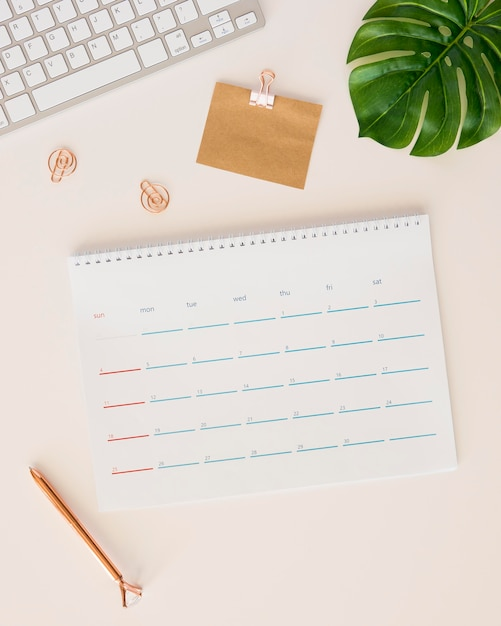 Flat lay desk calendar with monstera leaf and pencil box Free Photo