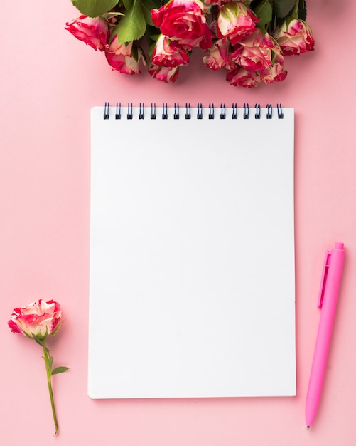 Flat lay of desk with bouquet of roses and notebook Free Photo