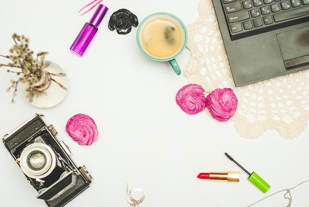 Flat lay- desk with coffee, zephyr, laptop, vintage camera and cosmetics Premium Photo