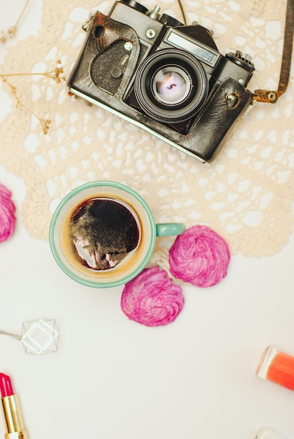 Flat lay- desk with coffee, zephyr, vintage camera and cosmetics Premium Photo
