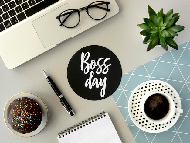 Flat lay desk with sign for boss day Premium Photo