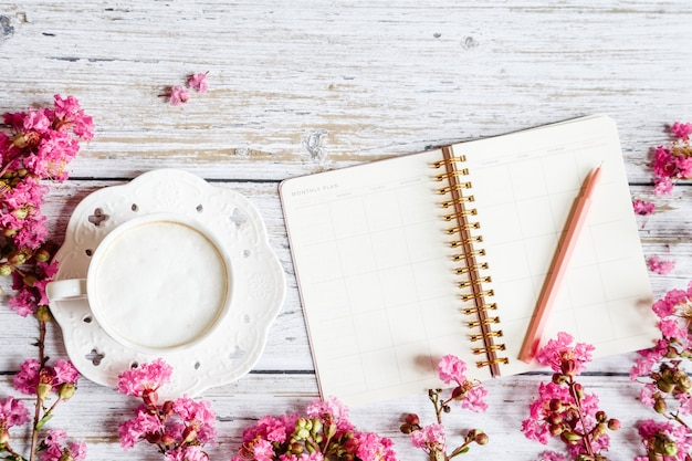 Flat lay desktop items: coffee mug, pen, notebook and pink flowers on white wooden table Premium Photo