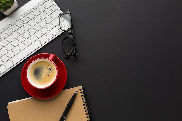 Flat lay of desktop with coffee cup and notebook Free Photo